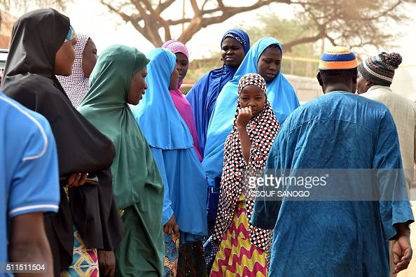 TOPSHOT People queue outside a polling station in Niamey during the country's presidential and legislative elections on February 21 2016 Voters in...