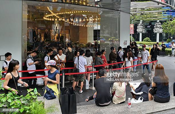 People queue outside a retail outlet for the latest limited edition clothing line at Orchard road shopping district in Singapore on November 6 2014...