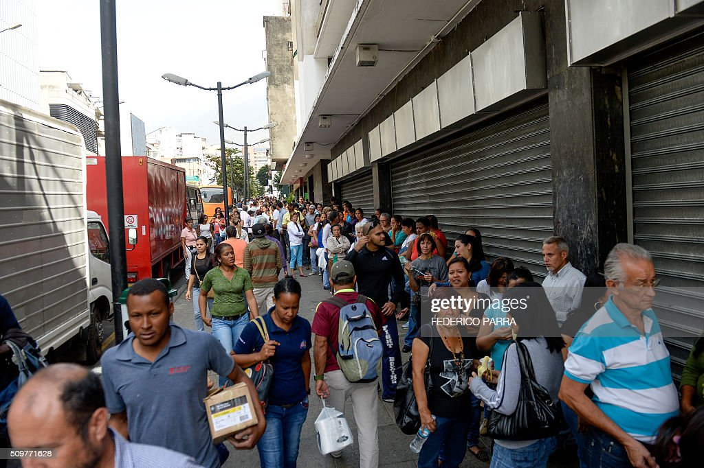People queue outside a supermarket in Caracas on February 12, 2016. Venezuela's opposition Friday vowed speeded-up moves to oust President Nicolas Maduro after he defied lawmakers by decreeing a state of economic emergency through the crisis-hit country's high court. 'In the next few days we will have to present a concrete proposal for the departure of that national disgrace that is the government,' the opposition leader of congress Henry Ramos told a news conference. He criticized a ruling on Thursday by the Supreme Court which approved Maduro's request for special powers to tackle a deepening economic crisis -- his latest maneuver in a tense political standoff. AFP PHOTO / FEDERICO PARRA / AFP / FEDERICO PARRA