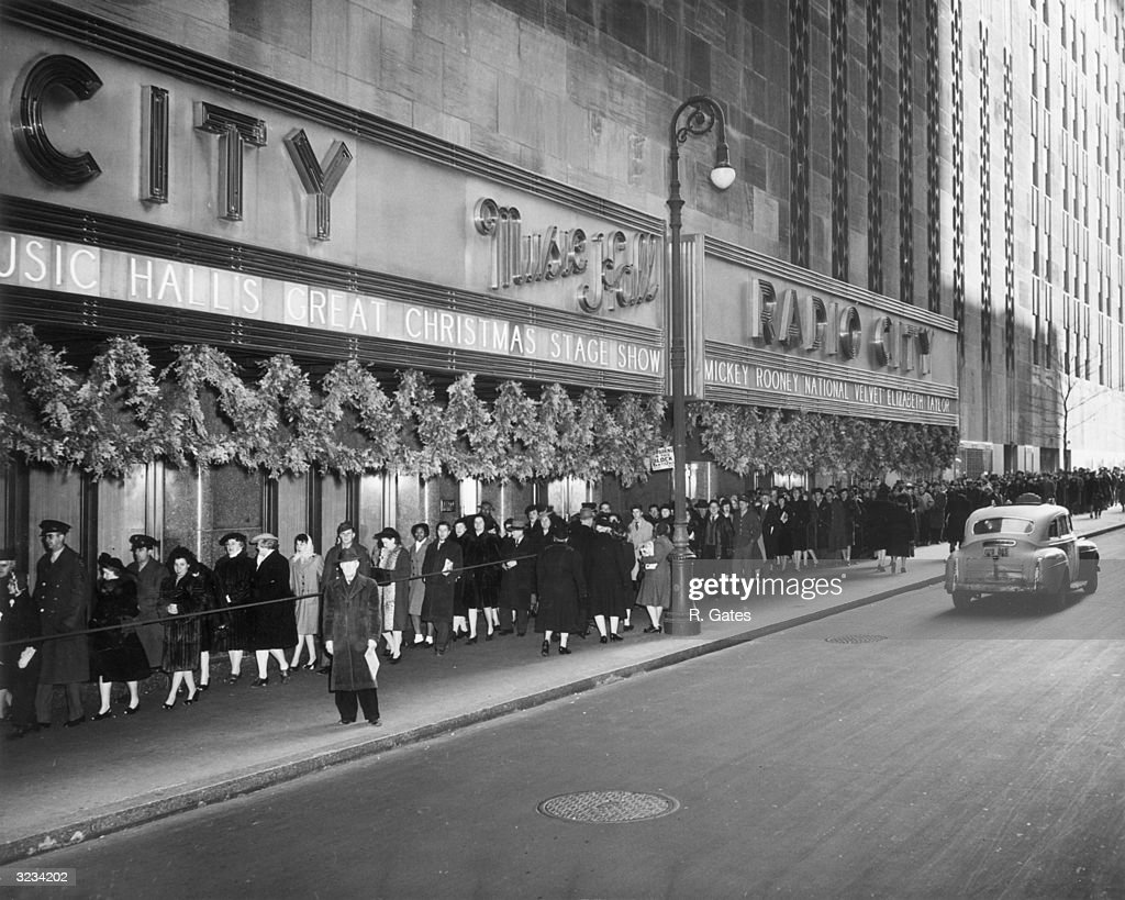 People queue outside Radio City Music Hall on 50th Street, Rockefeller Center, New York City. The Christmas Show and director Clarence Brown's film, 'National Velvet' are billed on the marquee.