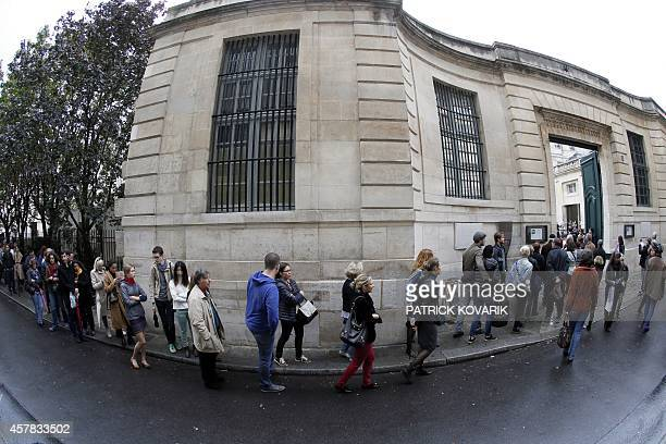People queue outside the Hotel Sale which host Paris's Picasso Museum on October 25 2014 in Paris on the day of its reopening after a fiveyear...