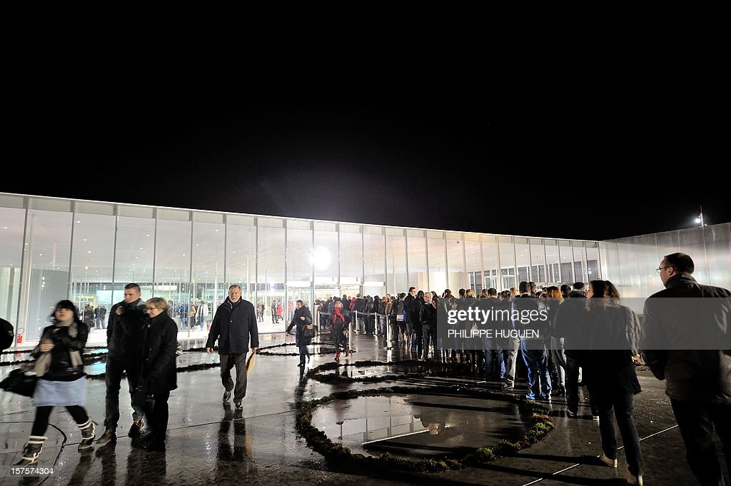 People queue outside the Louvre Museum on the first day of its opening to the public on December 4, 2012 in Lens, northern France. The Louvre museum opened a new satellite branch among the slag heaps of a former mining town Tuesday in a bid to bring high culture and visitors to one of France's poorest areas. Greeted by a group of former miners in overalls and hardhats, President Francois Hollande inaugurated today the Japanese-designed glass and polished-aluminium branch of the Louvre in the northern city of Lens. The 150 million euro ($196 million) project was 60 percent financed by regional authorities in the Nord-Pas-De-Calais region, on the English Channel and the border with Belgium.