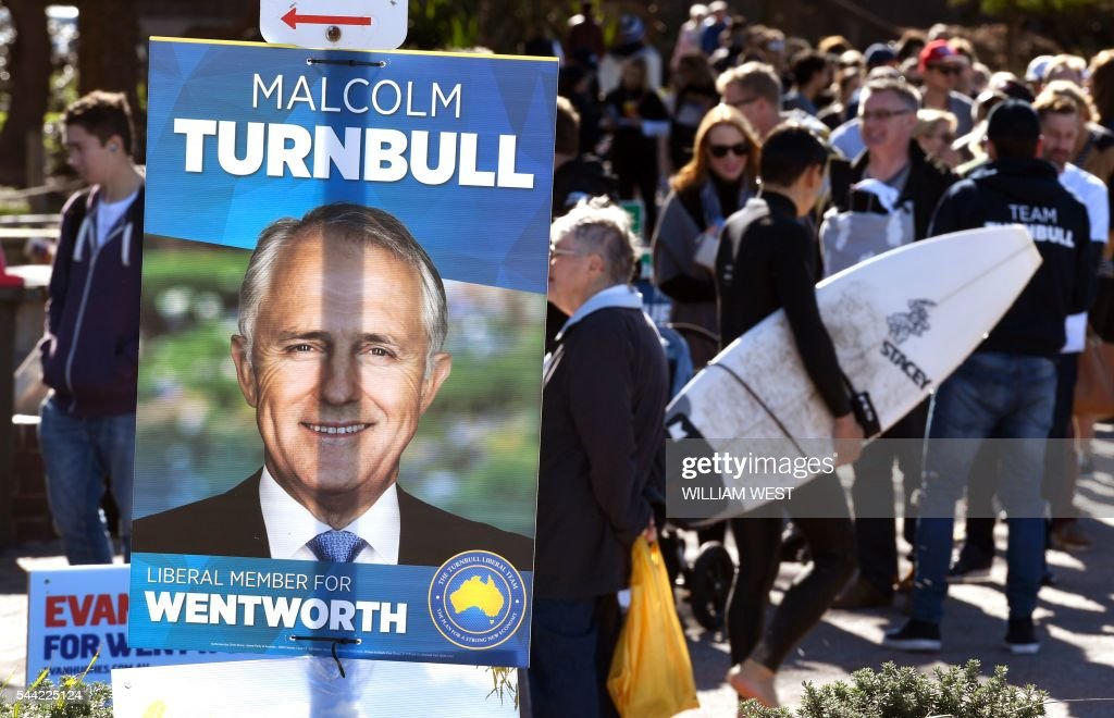 People queue past an election placard outside a voting station in the Sydney suburb of Bondi Beach on July 2, 2016. Australians flocked to vote in the national election with conservative leader Malcolm Turnbull appearing to have a slight edge over Labor's Bill Shorten, culminating a marathon race where economic management has become a key issue in the wake of the Brexit vote. / AFP / WILLIAM