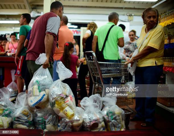 People queue to buy bags of basic foodstuff inside one of the food distribution centers called CLAP which are run by community leaders in a...