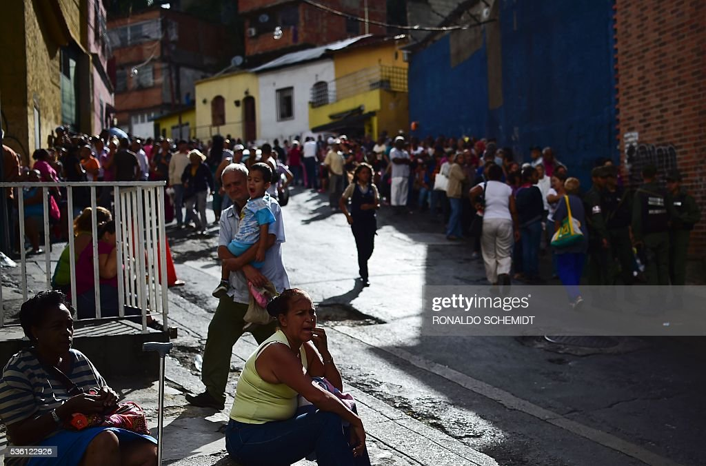 People queue to buy basic food and household items outside a supermarket in the poor neighbourhood of Lidice, in Caracas, Venezuela, on May 31, 2016. The oil-dependent nation faces severe food and medicine shortages, school closures and a cut in electricity production which has led to a dramatically shortened workweek for public sector employees. / AFP / RONALDO