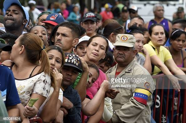 People queue to buy chicken behind a fence at a street market in Caracas on January 24 2015 With Venezuela's economy in crisis President Nicolas...