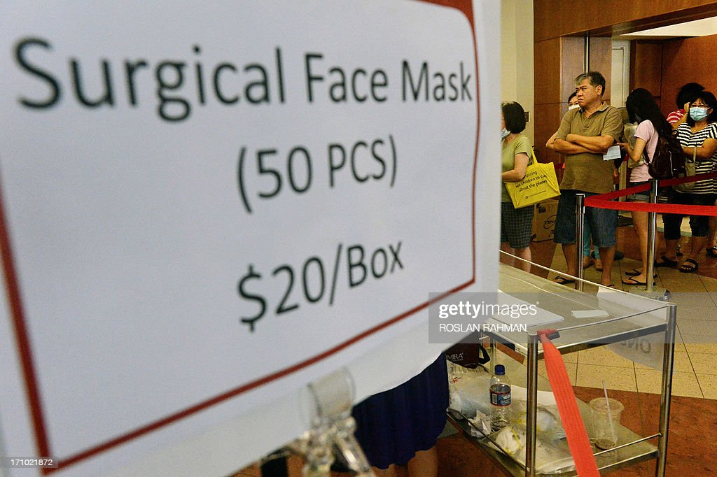 People queue to buy surgical face masks at a hospital in Singapore on June 21, 2013. Singapore's smog index hit the critical 400 level on June 21, making it potentially life-threatening to the ill and elderly people, according to a government monitoring site. AFP PHOTO/Roslan Rahman