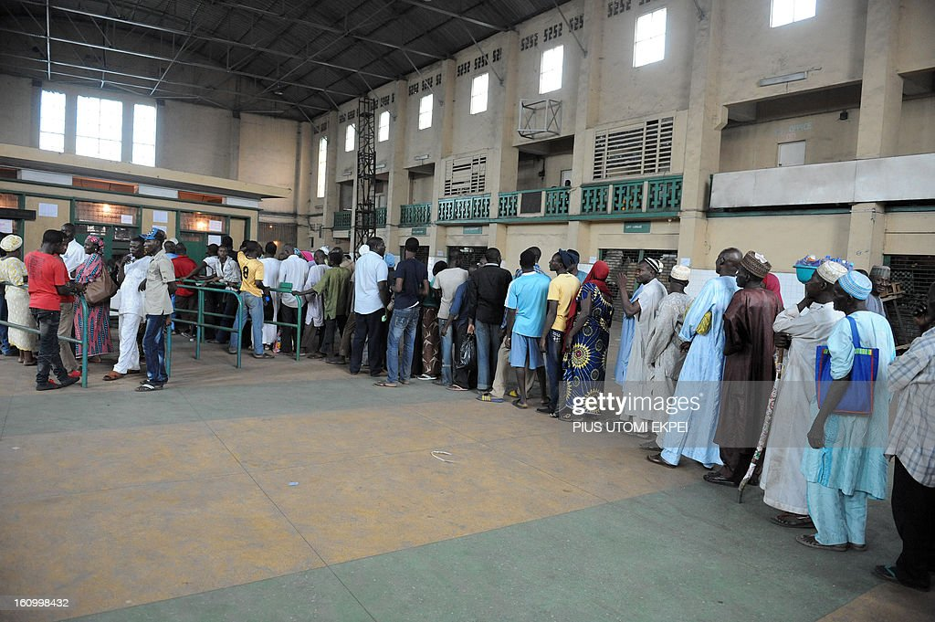 People queue to buy tickets at Lagos Terminus of the Nigerian Railway Corporation on February 8, 2013. The rejuvenated Nigerian Railway Corporation has commenced operation of mass transit on the Lagos-Kano route, Nigeria's major commercial cities. The state-owned corporation which went into bankruptcy during the last 20 years due to lack of maintenance of infrastructure and high numbers of employees also began haulage of petroleum products from Lagos to the north of the country. Earlier last year, the Railway Corporation had acquired 20 pressurised tank wagons as it prepared to commence the fuel haulage. The 20 wagons have the capacity to lift 900,000 litres of petroleum products, the equivalent of 27 road tankers. AFP PHOTO/PIUS UTOMI EKPEI.