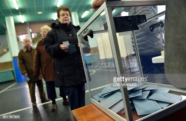 People queue to cast their ballots in a polling station during the second round of the regional election in the IledeFrance region on December 13...