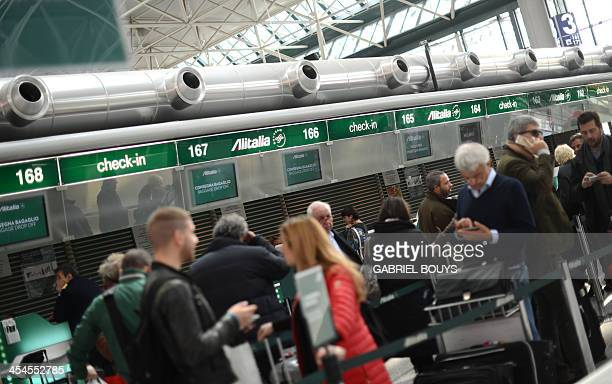 People queue to checkin at Alitalia's front desk on December 9 2013 at the Fiumicino airport near Rome Italian businessman Antonio Percassi said on...