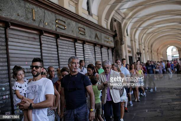 People queue to eat a dish of spaghetti all'amatriciana during a charity event in Piazza San Carlo in Turin on August 28 whose profits are to help...