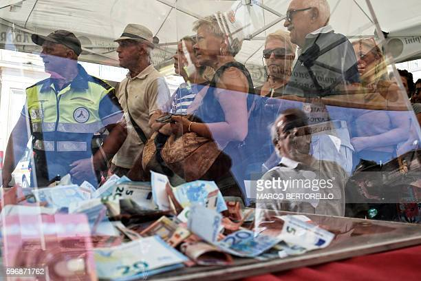 People queue to eat a dish of spaghetti all'amatriciana next to a donation box during a charity event in Piazza San Carlo in Turin on August 28 whose...