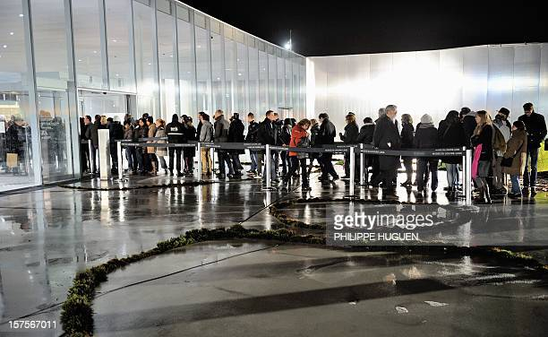 People queue to enter the Louvre Museum on the first day of its opening to the public on December 4 2012 in Lens northern France The Louvre museum...