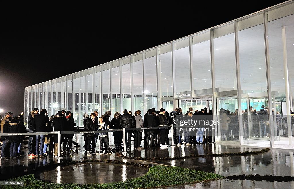 People queue to enter the Louvre Museum on the first day of its opening to the public on December 4, 2012 in Lens, northern France. The Louvre museum opened a new satellite branch among the slag heaps of a former mining town Tuesday in a bid to bring high culture and visitors to one of France's poorest areas. Greeted by a group of former miners in overalls and hardhats, President Francois Hollande inaugurated today the Japanese-designed glass and polished-aluminium branch of the Louvre in the northern city of Lens. The 150 million euro ($196 million) project was 60 percent financed by regional authorities in the Nord-Pas-De-Calais region, on the English Channel and the border with Belgium. AFP PHOTO PHILIPPE HUGUEN