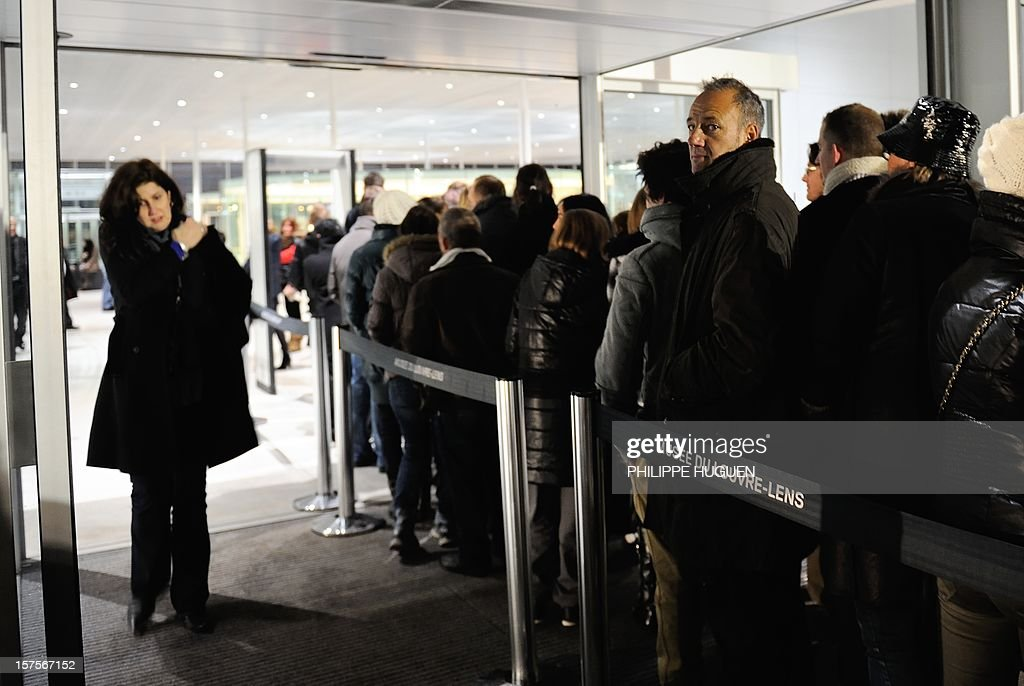 People queue to enter the Louvre Museum on the first day of its opening to the public on December 4, 2012 in Lens, northern France. The Louvre museum opened a new satellite branch among the slag heaps of a former mining town Tuesday in a bid to bring high culture and visitors to one of France's poorest areas. Greeted by a group of former miners in overalls and hardhats, President Francois Hollande inaugurated today the Japanese-designed glass and polished-aluminium branch of the Louvre in the northern city of Lens. The 150 million euro ($196 million) project was 60 percent financed by regional authorities in the Nord-Pas-De-Calais region, on the English Channel and the border with Belgium.