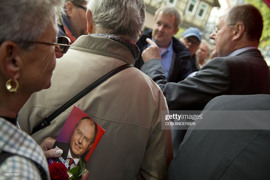 People queue to get autograph from Peer Steinbrueck, Chancellor candidate of the German Social Democrat party (SPD), canvassing in the pedestrian shopping area of the central German town of Peine on September 16, 2013. German voters go to the polls on September 22, 2013 for the general elections.