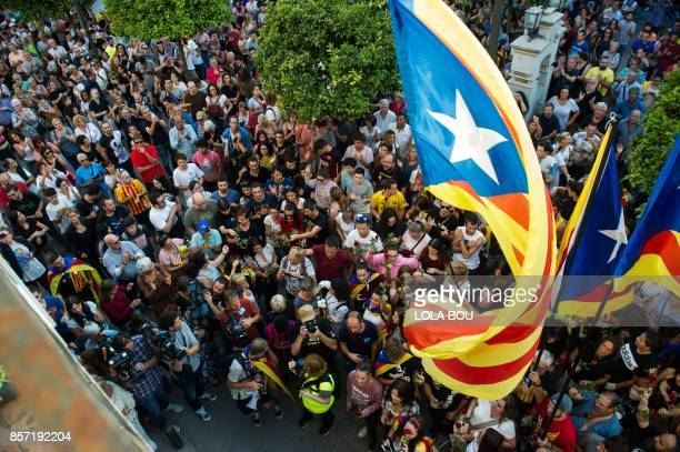 People queue to lay flowers in front of ballot boxes used during the Catalan independence referendum in Pineda de Mar on October 3 during a general...