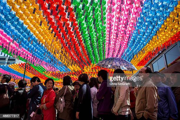 People queue to pay their respects underneath lines of lanterns after the Vesak Buddhist Ceremony celebrating Buddha's birth at the Jogyesa Temple on...