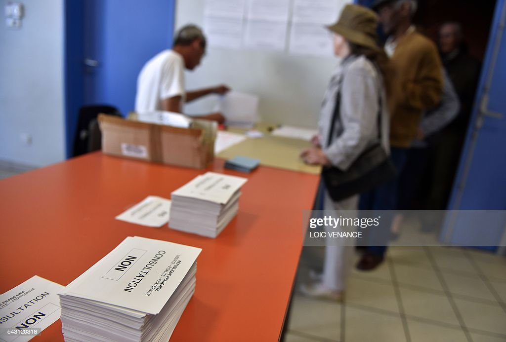 People queue to pick up their ballot paper before casting their vote on June 26, 2016, in Notre-Dame-des-Landes during a local referendum organised in Loire-Atlantique on subject of the Notre-Dame-des-Landes' airport project. Nearly One million people living in France's Loire-Atlantique department are voting in a referendum which poses the question 'Are you in favour of the project to transfer the Nantes-Atlantique airport to the municipality of de Notre-Dame-des-Landes?' to voters. The referendum was organised by the French executive power hoping to find a solution to the issue which has dragged on for 50 years. / AFP / LOIC