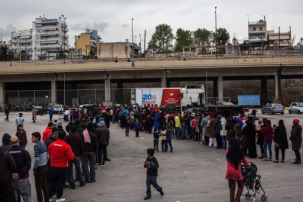 People queue to receive some food outside a passenger terminal used as shelter for refugees and migrants at the Piraeus harbour in Athens on March 12, 2016. Greece aims to deal swiftly with the mig...