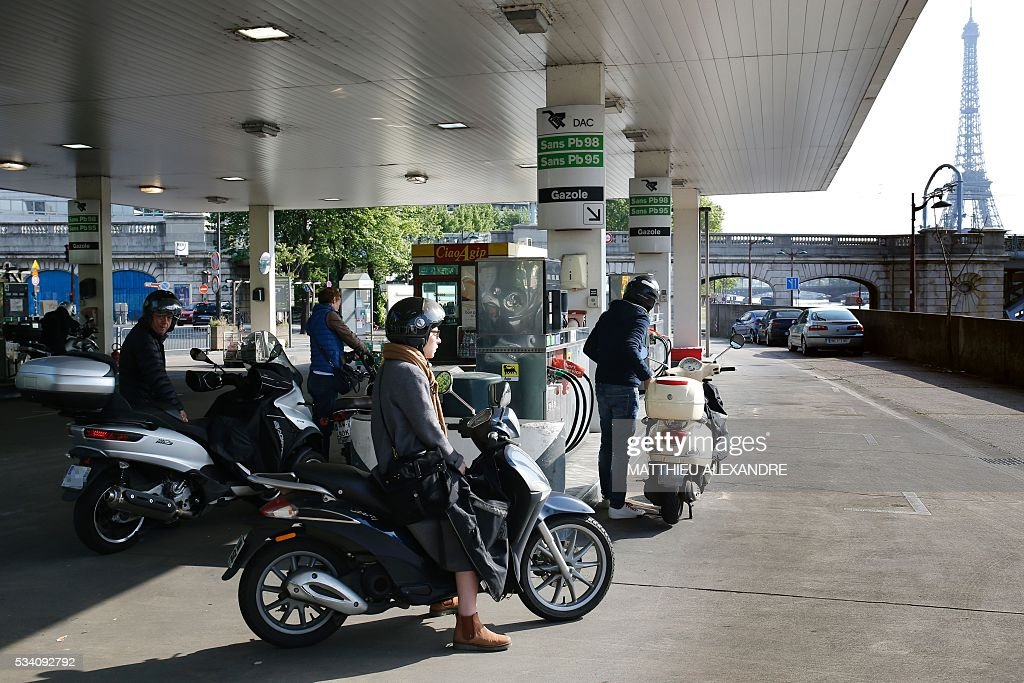 People queue to refill their fuel tank on May 25, 2016 in Paris as a union blockade of refineries and fuel depots continues. France has been using strategic fuel reserves for two days in the face of widespread blockades of oil depots by union activists, the head of the oil industry federation said on May 25, 2016. ALEXANDRE