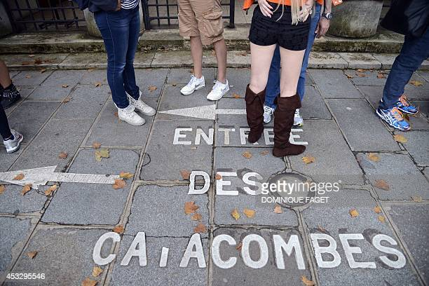 People queue to visit the Catacombs of Paris on August 7 2014 which hold over six million skulls and bones These underground quarries were used to...