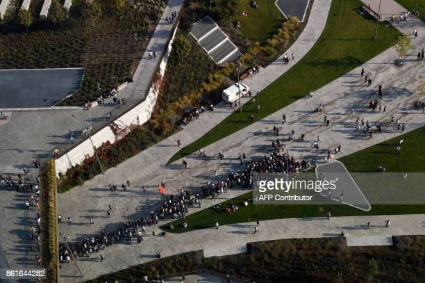 People queue to visit the Generali tower also called Hadid tower designed by Zaha Hadid studio in the Citylife neighborghood western Milan on October...