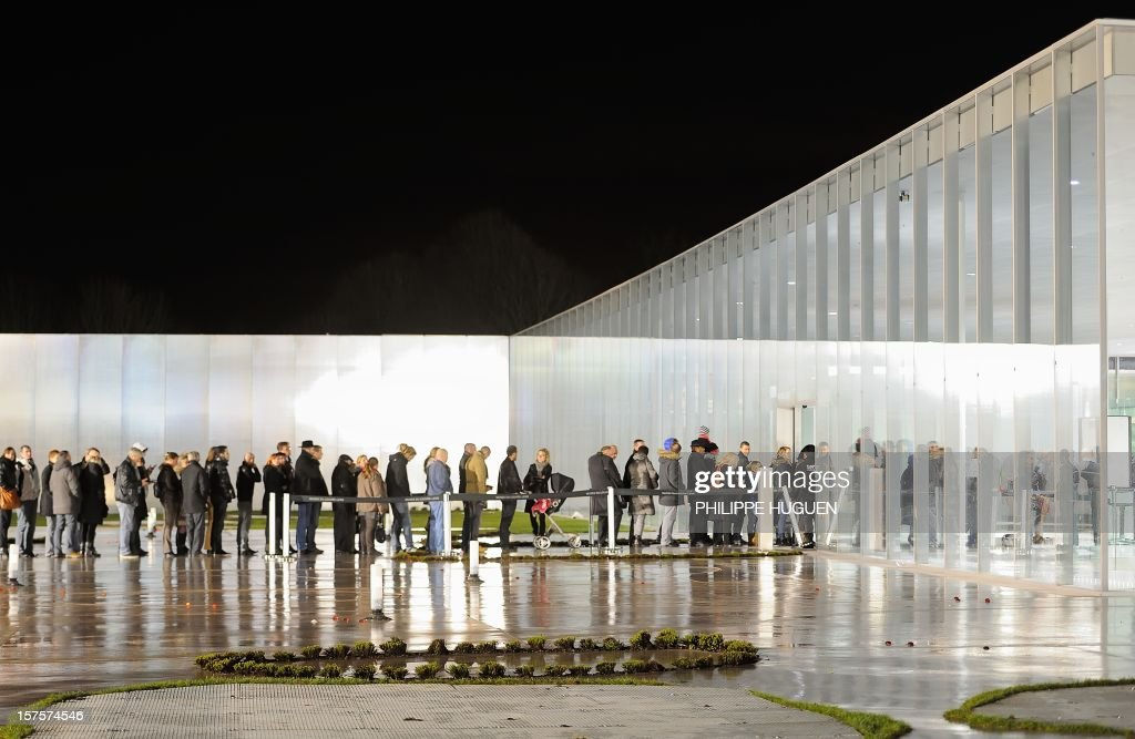People queue to visit the Louvre Museum on the first day of its opening to the public on December 4, 2012 in Lens, northern France. The Louvre museum opened a new satellite branch among the slag heaps of a former mining town Tuesday in a bid to bring high culture and visitors to one of France's poorest areas. Greeted by a group of former miners in overalls and hardhats, President Francois Hollande inaugurated today the Japanese-designed glass and polished-aluminium branch of the Louvre in the northern city of Lens. The 150 million euro ($196 million) project was 60 percent financed by regional authorities in the Nord-Pas-De-Calais region, on the English Channel and the border with Belgium.
