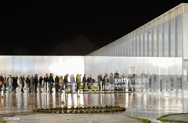 People queue to visit the Louvre Museum on the first day of its opening to the public on December 4 2012 in Lens northern France The Louvre museum...