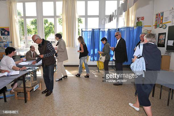 People queue to vote for the second round of the French parliamentary elections on June 17 at a polling station in the western city of Nantes French...