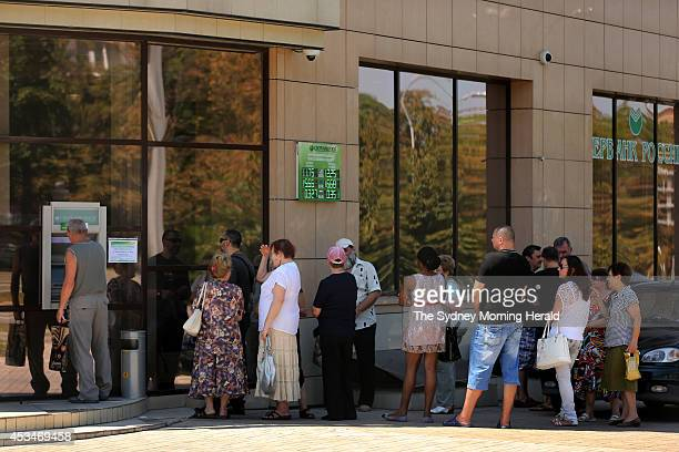 People queue to withdraw cash from a teller machine at a bank in Donetsk Ukraine during ongoing conflict between Pro Russian rebels and the Ukrainian...