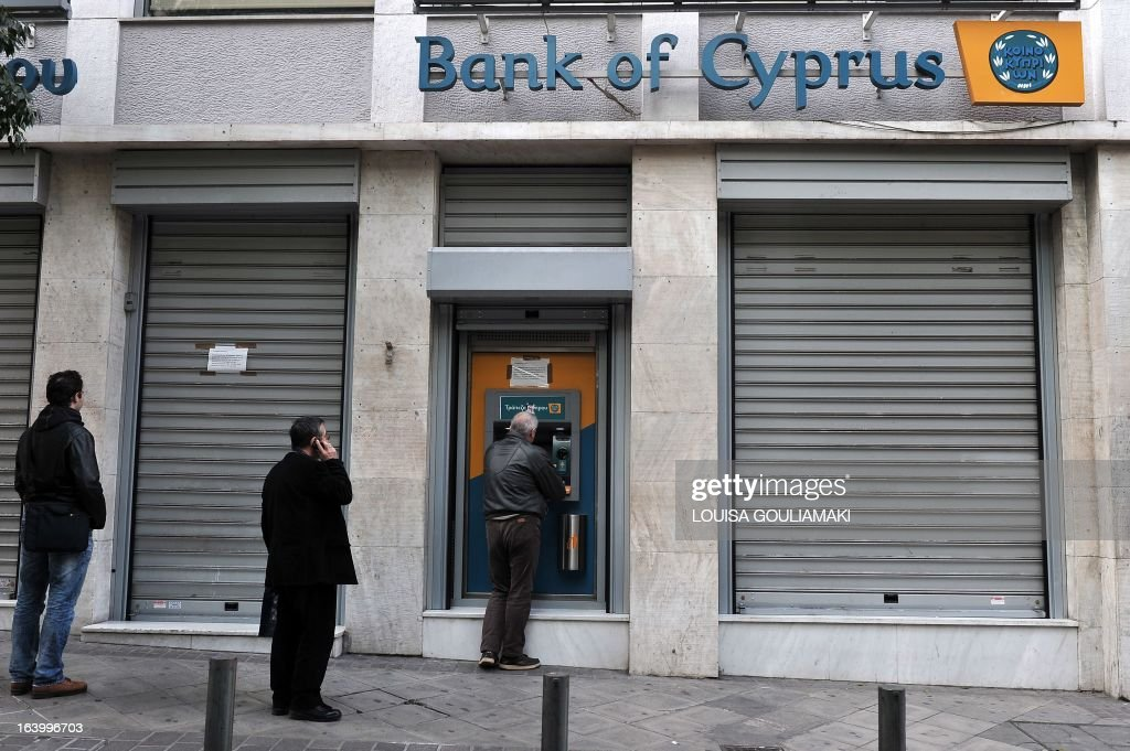 People queue to withdraw money from a Bank of Cyprus branch' ATM in Athens on March 19, 2013 while Cypriot banks remain closed in Greece until March 21. Athens was 'ready' to absorb the subsidiaries of three Cyprus banks active in Greece, the Greek finance minister said as the eurozone sought to amend a controversial levy on the island nation's bank deposits. AFP PHOTO / LOUISA GOULIAMAKI