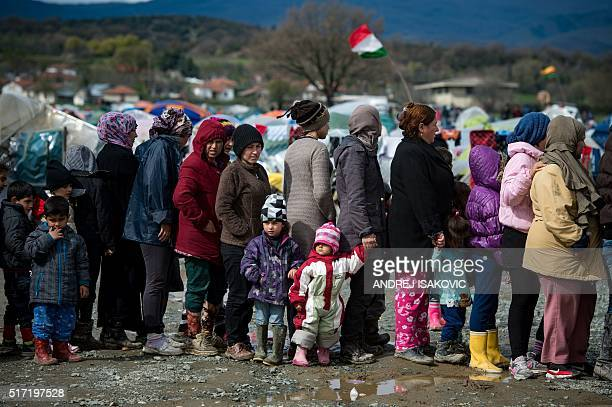 People queue up for food distributed at a makeshift camp occupied by migrants and refugees at the GreekMacedonian border near the village of Idomeni...