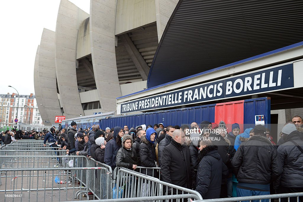 People queue up in front of the Paris Parc des Princes stadium, on March 18, 2013 in Paris, to buy tickets to attend the Champions League quarter final match between Paris Saint-Germain and FC Barcelone scheduled on April 2, in this stadium. AFP PHOTO MARTIN BUREAU