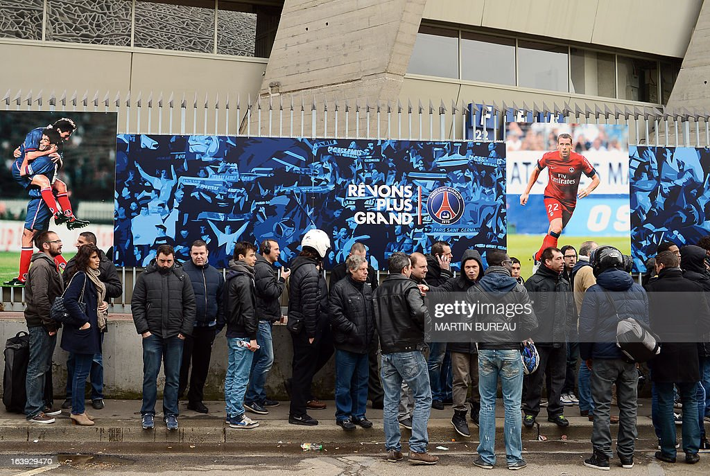 People queue up in front of the Paris Parc des Princes stadium, on March 18, 2013 in Paris, to buy tickets to attend the Champions League quarter final match between Paris Saint-Germain and FC Barcelone scheduled on April 2, in this stadium. At background, the banner reads : 'Dream bigger'.