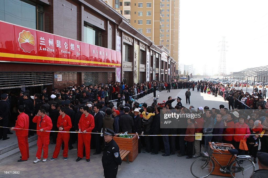 People queue up outside a gas station to buy natural gas in Lanzhou, northwest China's Gansu province, on March 27, 2013 fearing the price will rise in April. China's Price Watchdag denied the rumor sweeping the media that the gas price will rise by one yuan per cubic meter in April, state media reported. CHINA OUT AFP PHOTO