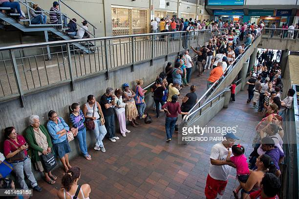 People queue up outside a supermarket in Caracas on January 13 2015 Venezuela suffers a shortage of almost a third of commodities inflation of 64% in...