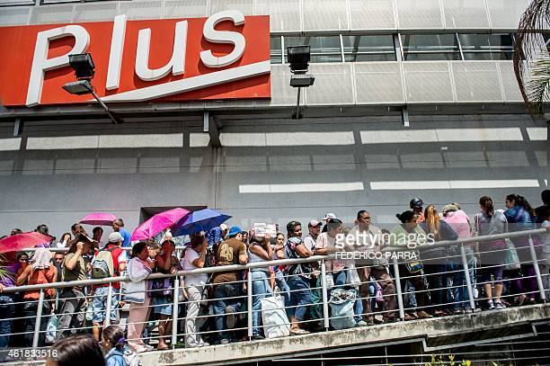 People queue up outside a supermarket in Caracas on January 20 2015 Venezuela suffers from shortages of nearly a third of all basic goods inflation...