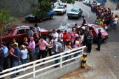 People queue up outside a supermarket to buy food in Caracas April 2 2014 The Venezuelan government will launch an electronic card to identify...