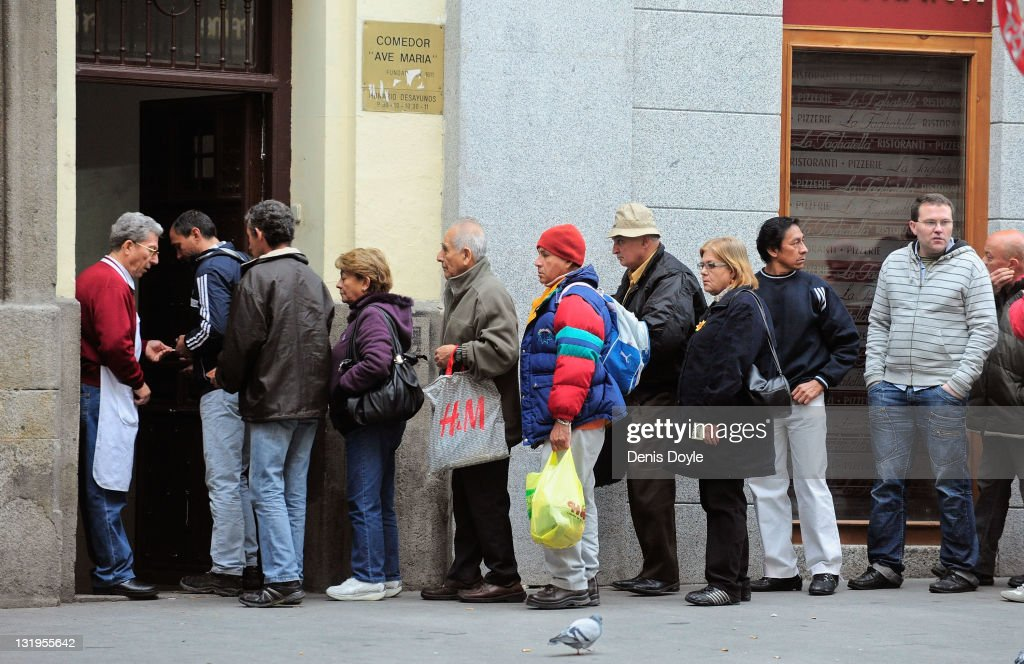 People queue up outside the Ave Maria charity food centre on November 9, 2011 in Madrid, Spain. Poor people and homeless are given a free breakfast at the centre run by the Fundacion Real Congregacion de Esclavos del Dulce Nombre de Maria. Spain goes to the polls on November 20, 2011, while facing economic stagnation and the highest unemployment rate in Europe.