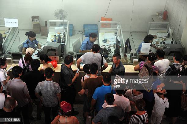 People queue up to buy tickets at the counter in the ticket hall of Hefei railway station in Hefei north China's Anhui province on July 1 2013...