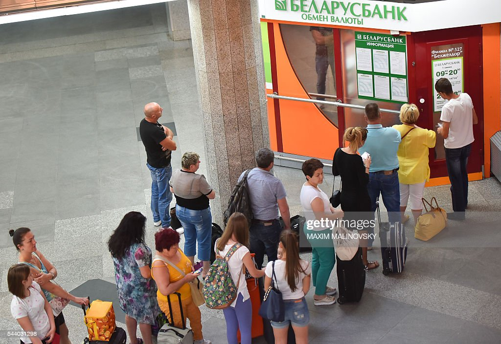 People queue up to change money at the currency exchange office of the Belarus bank at the railway station in Minsk on July 1, 2016. Belarus is slashing four zeros from banknotes, the central bank said on June 30, in a move authorities hope will curb inflation. New banknotes, ranging from 5 to 500 Belarusian ruble notes, are put in circulation on July 1, the bank said. The Belarussian ruble - which currently stands at close to 20,200 to the US dollar (22,450 to the euro) - has suffered heavily from inflation in recent years together with the nation's centralised economy. MALINOVSKY