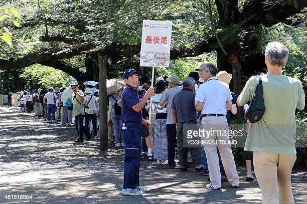 People queue up to see a giant Titan Arum at the Jindai botanical gardens in Tokyo on July 22 2015 after the flower started to bloom on July 21 The...