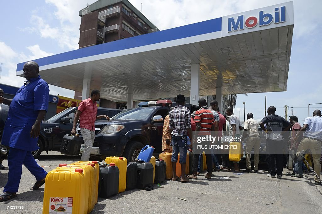 People queue with jerrycans to buy fuel at Mobil filling station in Lagos on May 21 2015 Long queues formed at petrol stations across oilrich Nigeria...