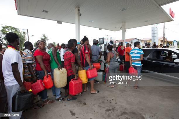 People queue with with jerrycans after a tank truck was able to resupply an outoffuel petrol station on March 26 in Cayenne French Guiana during a...
