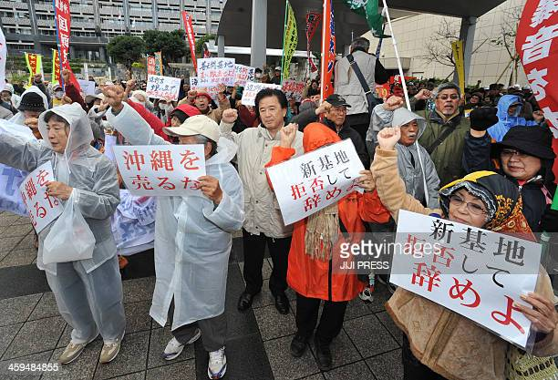 People raise their arms and shout slogans during a rally denouncing the relocation of a US military base in front of the Okinawa prefectural office...