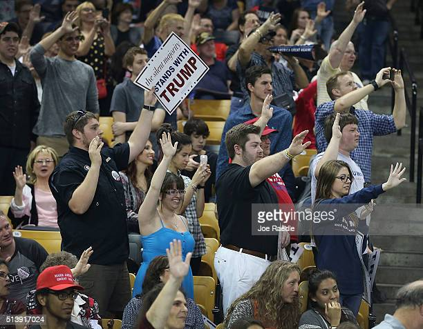 People raise their arms as Republican presidential candidate Donald Trump ask them to pledge that they will vote for him during a campaig rally at...