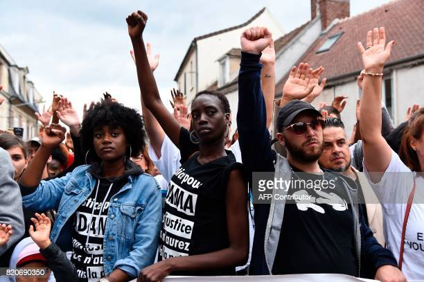 People raise their fists as they take part in a march in memory of Adama Traore who died during his arrest by the police in July 2016 on July 22 2017...