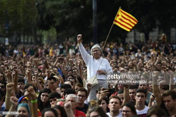 TOPSHOT People raise their fists during a protest in Barcelona on October 2 2017 a day after hundreds were injured in a police crackdown during...