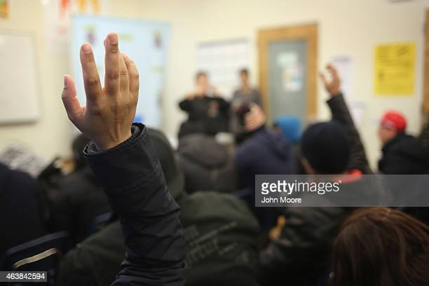 People raise their hands as Immigrants attend a workshop for Deferred Action for Childhood Arrivals on February 18 2015 in New York City The...